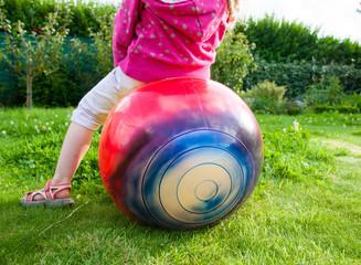 Little gilrl jumping on ball