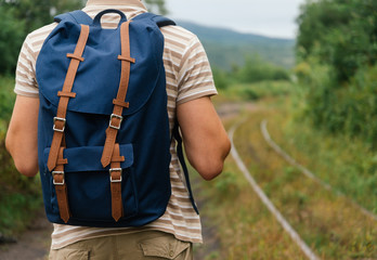 Hiker man with backpack going on path in summer