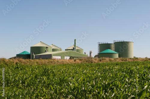 Leinwanddruck Bild Biogasanlage mit Maisfeld
