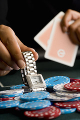Woman placing watch on pile of gambling chips on table, close-up
