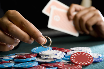 Woman placing ring on pile of gambling chips on table, mid section