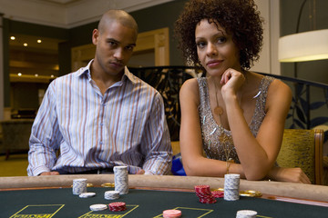 Young man and woman gambling at poker table, portrait