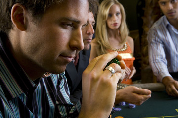 Man with gambling chips at table, side view