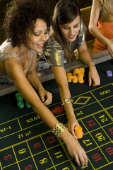 Woman and friend placing gambling chips on roulette table, elevated view