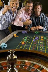 Young man and friends gambling at roulette table in casino, smiling