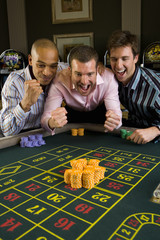Young man with friends gambling at roulette table in casino, smiling