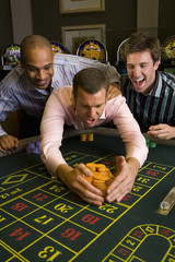 Young man with friends collecting pile of gambling chips from roulette table in casino, smiling
