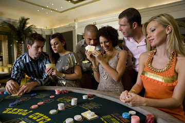 Young men and women gambling at poker table in casino, smiling