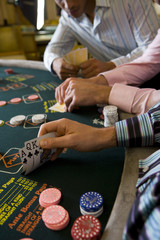 Young men gambling at poker table in casino, section