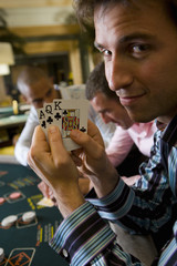 Young man gambling at poker table in casino, showing cards, smiling, portrait