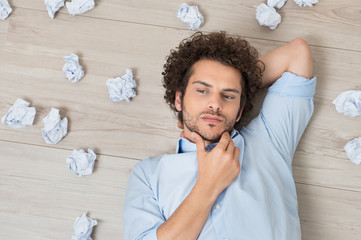 Man With Crumpled Papers Lying On Floor