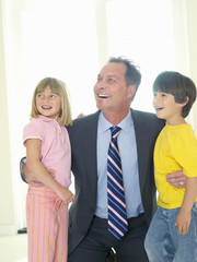 Businessman embracing son and daughter (4-8), smiling
