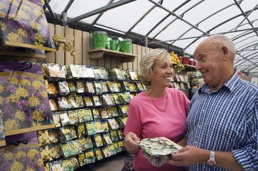 Senior couple shopping in garden centre, holding pack of flower bulbs, smiling
