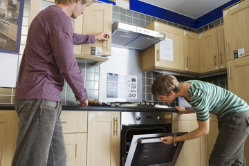 Couple looking at new kitchen in home furnishings store, man opening cupboard, woman checking oven