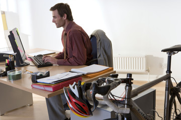 Man at desk in office, side view