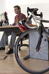Bicycle by man at desk in office, low angle view