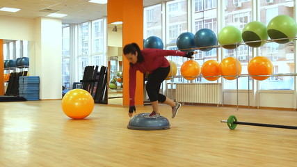 Young woman doing fitness exercise with bosu ball