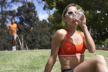 Woman sitting on grass in park, drinking from water bottle, man jogging, focus on foreground