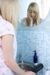 Young woman at mirror in bathroom