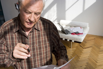 Senior man with paperwork and hands-free device