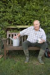 Senior man with watering can on bench, portrait