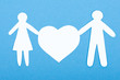 Closeup of paper people with a big heart on white background