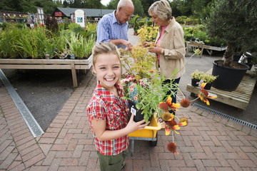 Girl (7-9) holding pot plant in garden centre, smiling, portrait, grandparents in background