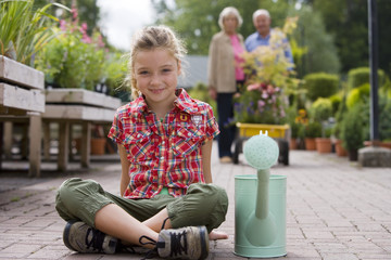 Girl (7-9) sitting with watering can in garden centre, smiling, portrait, grandparents in background