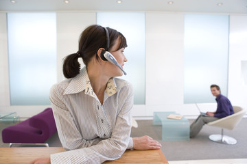 Businesswoman with headset, colleague in background