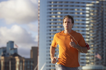 USA, California, San Diego, man jogging, listening to MP3 player strapped to arm