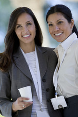 Two businesswoman posing with conference badges