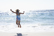 Girl (3-5) wearing swimsuit, jumping above surf on sandy beach, rear view, sea shimmering in sunlight