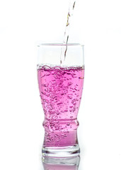 Pink water splashing from glass