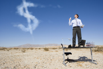 Businessman seeing dollar sign in clouds