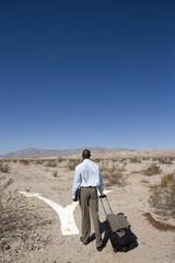 Businessman walking through desert
