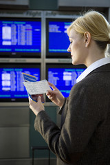 Businessman checking boarding pass in airport