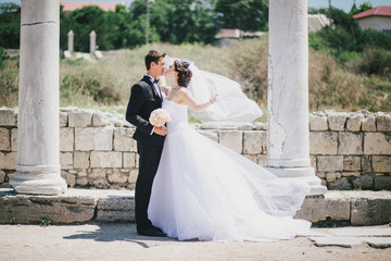 Happy bride and groom posing on the background of  ancient ruins