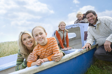 Young family sitting in boat at beach