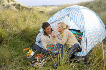 Young couple eating at campsite