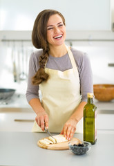 Happy young housewife cutting cheese in kitchen