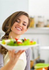 Portrait of happy young housewife showing salad