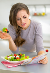 Young woman eating greek salad in kitchen and reading magazine