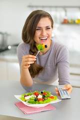 Young woman eating greek salad and watching tv