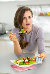 Surprised young woman eating greek salad and watching tv