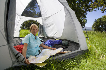 Woman looking at map in tent