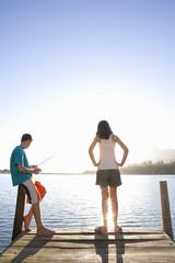 Teenagers fishing off dock