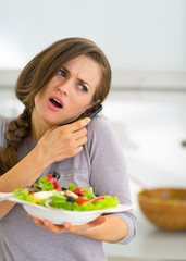 Concerned young woman with vegetable salad talking mobile phone