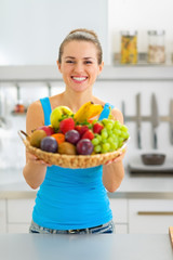 Smiling young woman showing fruits plate