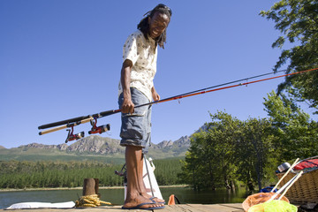 Man holding fishing pole on dock