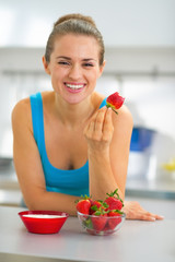 Happy young woman eating strawberry with yogurt in kitchen
